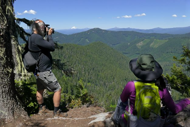 From the other direction, on Lowder, Gary and Meng-ting admire the view of Horsepasture in the foreground center and Mount Jefferson, Three Fingered Jack, and Mount Washington in the distance.